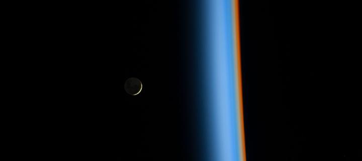 Crescent moon rising and the cusp of Earth's atmosphere